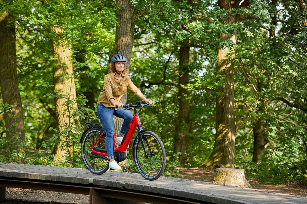 Frau mit Helm auf rotem Fahrrad