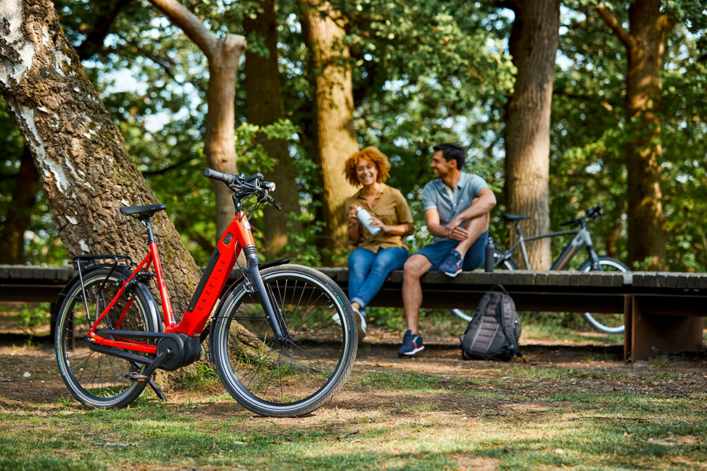 Mann und Frau mit rotem Fahrrad