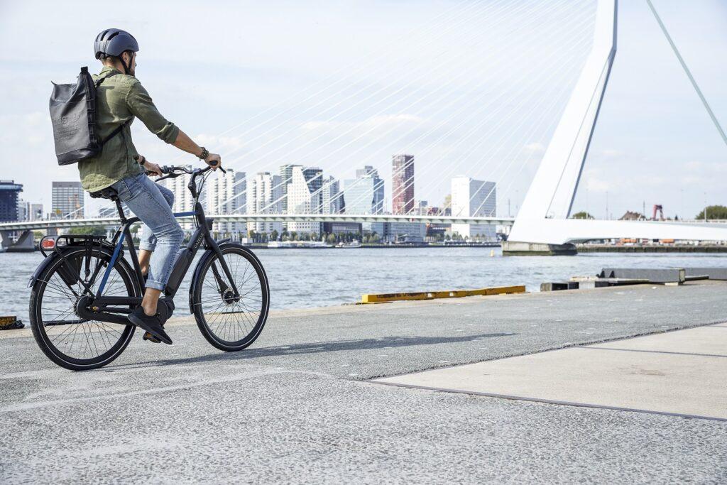 Mann mit Rucksack auf schwarz-blauem Fahrrad