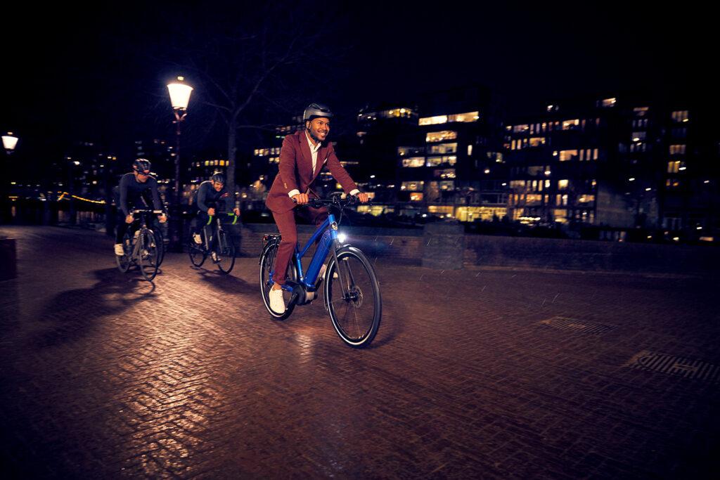Mann auf blauem Fahrrad im Dunkeln